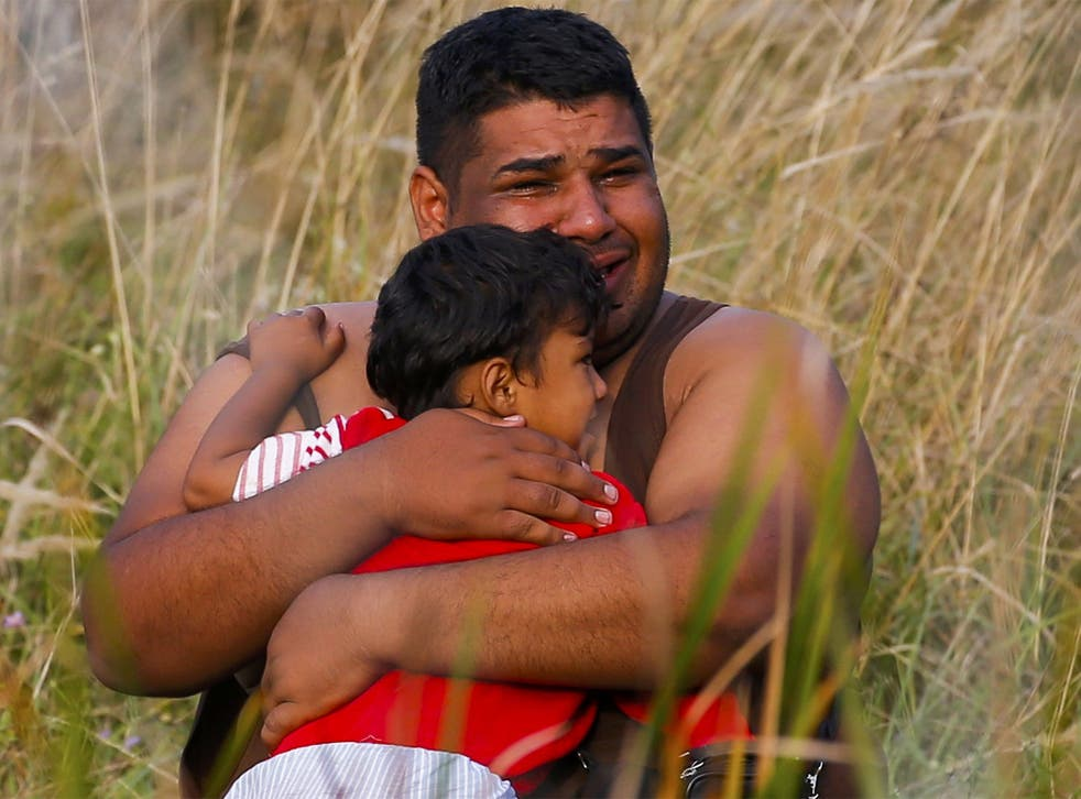 A refugee cries as he holds a child on the Serbian side of the border with Hungary in Asotthalom