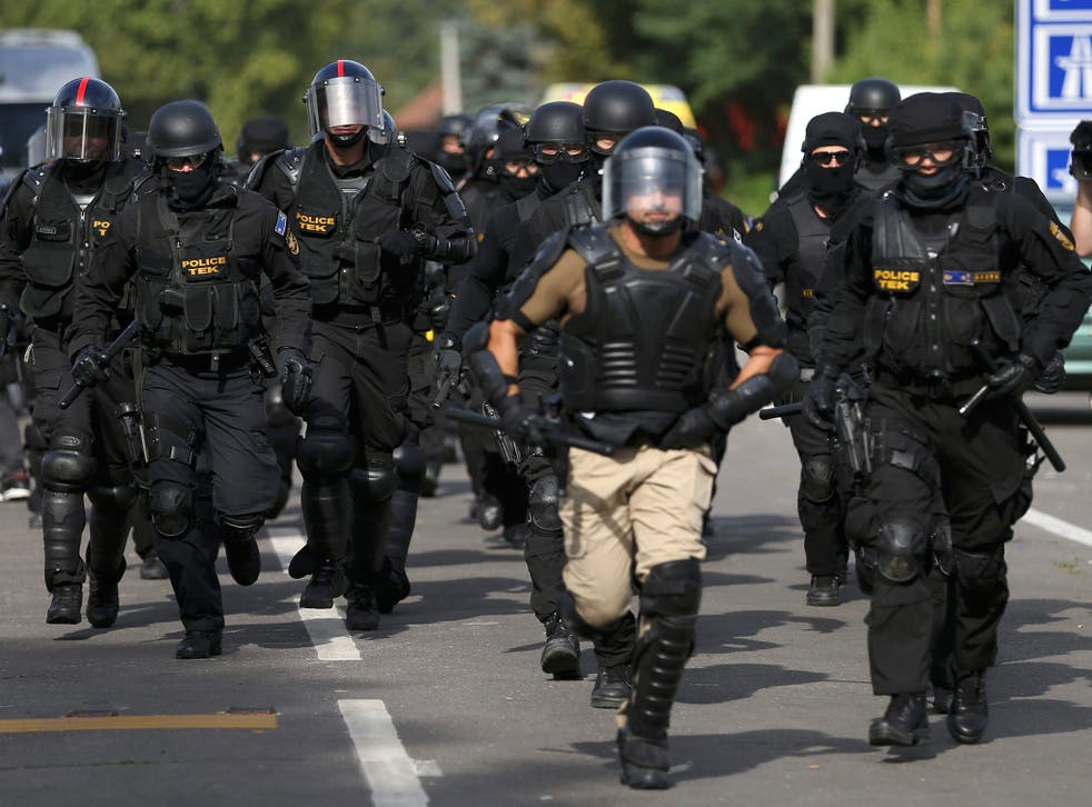 Hungarian riot policemen run as they are deployed at the border crossing with Serbia in Roszke