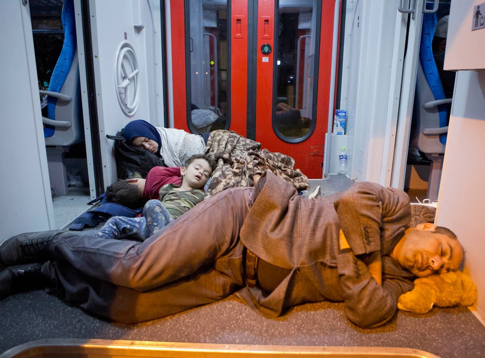 Refugees rest in a train at the railway station in Beli Manastir, near the Hungarian border, northeast Croatia, early Friday, Sept. 18, 2015
