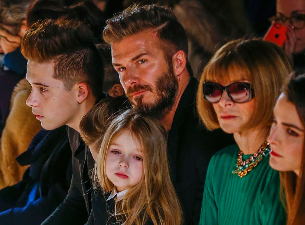 Former England captain David Beckham sits next to U.S. Vogue editor Anna Wintour (2nd R) with his daughter, Harper, on his lap and son Brooklyn (L) during a presentation of the Victoria Beckham Fall/Winter 2015 collection during New York Fashion Week Febr