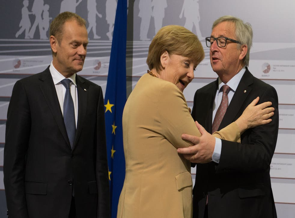 Angela Merkel hugs Jean-Claude Juncker, the EU Commission President, as European Council president Donald Tusk looks on (PA)