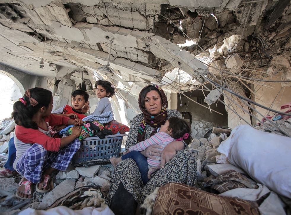 A family in their destroyed home in Kobani, where Kurdish YPG forces helped to defeat Isis