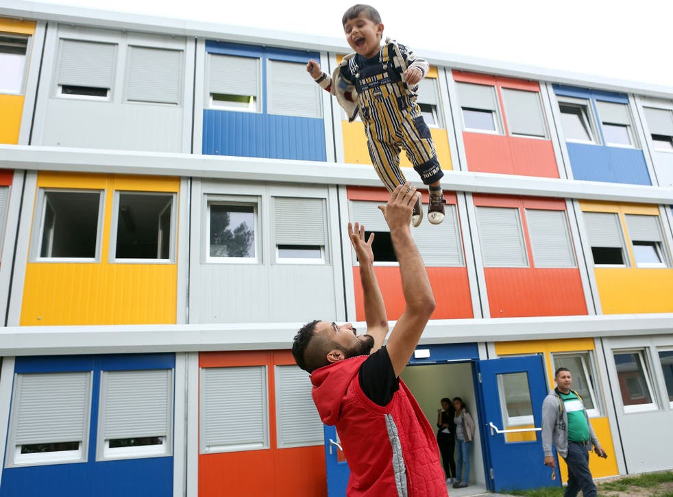 A Syrian refugee plays with his child at a temporary shelter made from shipping containers in Berlin