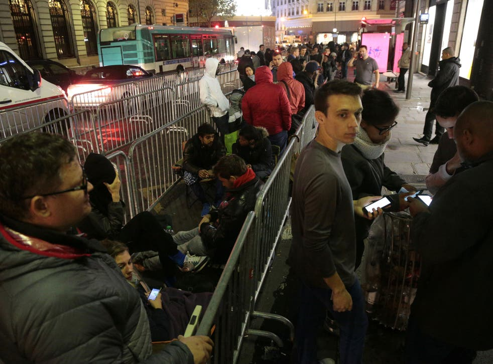 People wait to enter an Apple store on the day of the official launch of the iPhone 6s, on September 25, 2015 in Paris