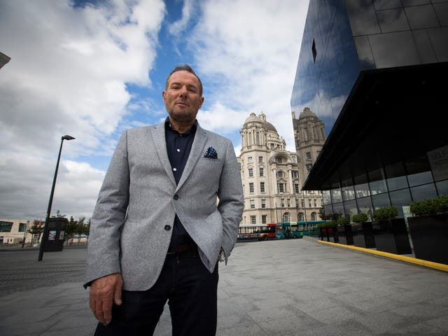 Former left-wing British politician, Derek Hatton, pictured in his home city of Liverpool, with the iconic Liver Building in the background.