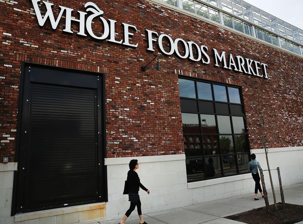 People walk past a Whole Foods Market in Brooklyn.