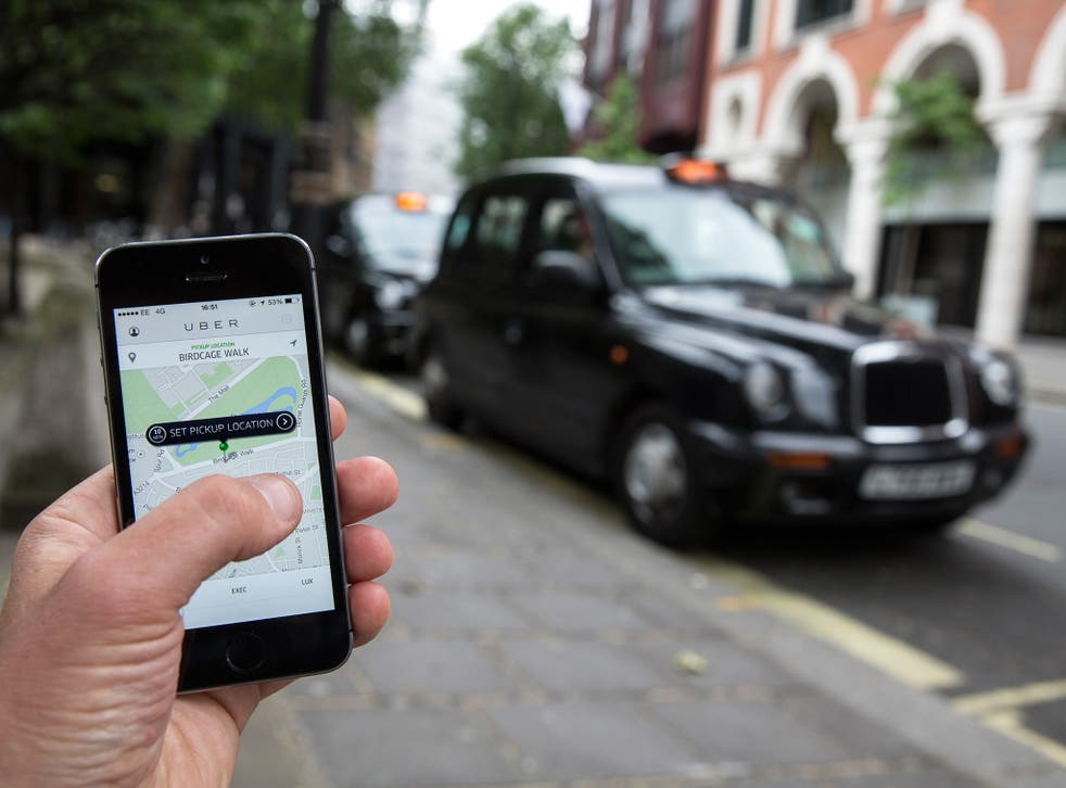 A smartphone displays the 'Uber' mobile application which allows users to hail private-hire cars from any location