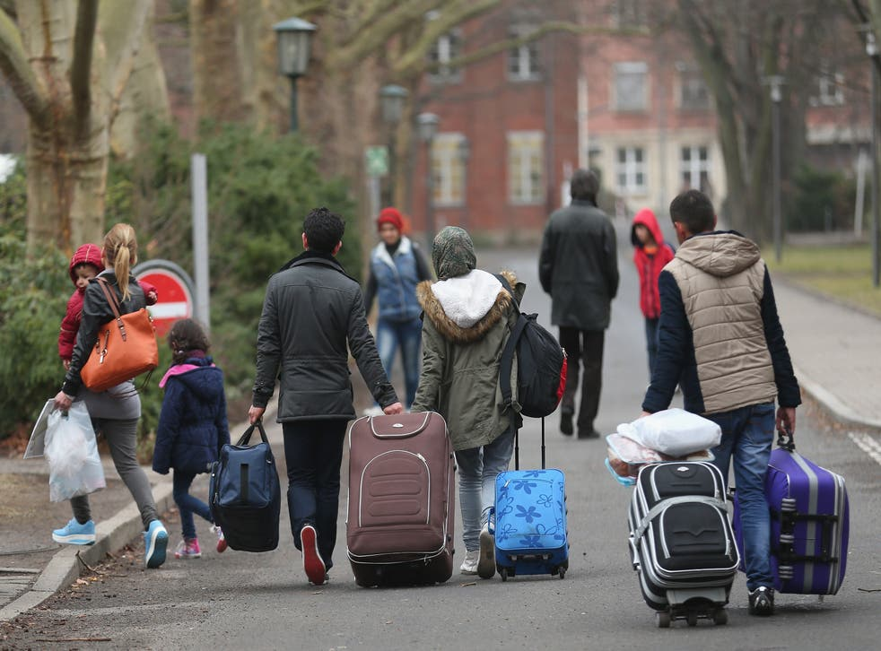 People pulling suitcases arrive at the Berlin refugee registration centre
