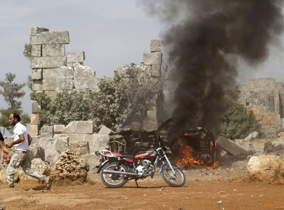 A man runs past a burning military vehicle at a base controlled by rebel fighters from the Ahrar al-Sham Movement, that was targeted by what activists said were Russian airstrikes at Hass ancient cemeteries in the southern countryside of Idlib, Syria