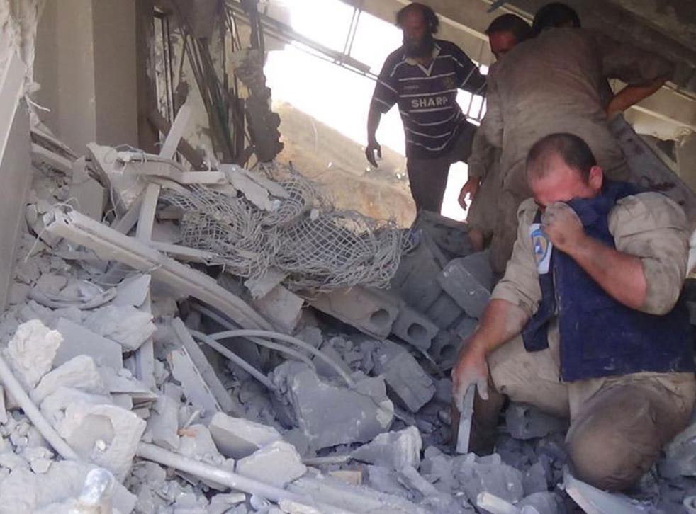 Civil defence workers in the aftermath of the Russian air strike on Talbiseh, Syria, which killed dozens of civilians