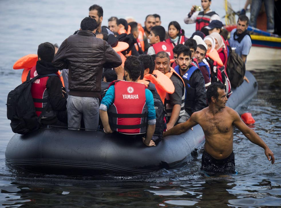 Refugees traveling by overloaded rubber dinghy from Turkey arrive at the coast near Mytilene, Lesbos