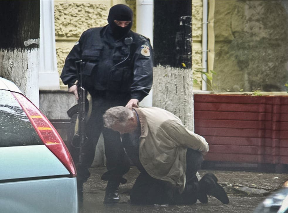Go-between Teodor Chetrus is held by Moldovan police during a uranium-235 sting operation