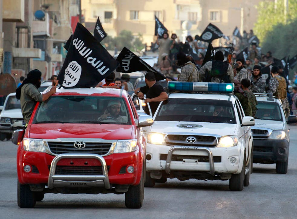 Isis fighters waving flags travel in Toyota vehicles as they take part in a military parade along the streets of Syria's northern Raqqa province