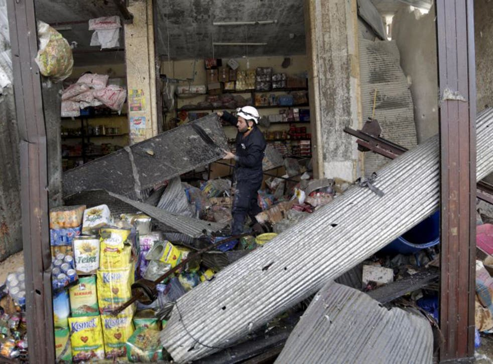 A civil defence member looks for survivors in a damaged shop at a site hit by what activists said was an air strike by forces of Syria's President Bashar al-Assad,