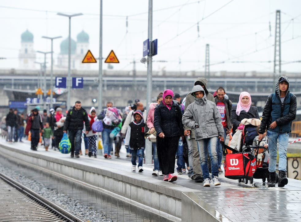 Refugees walk along the platform at the train station in Passau, Germany