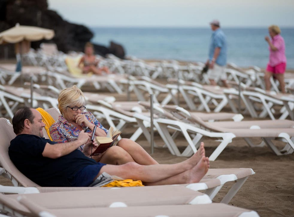 Tourists relax on Puerto del Carmen beach on April 12, 2014 in Lanzarote, Spain. Lanzarote, , is a popular destination for British tourists and is just 37 miles long and 12 miles wide
