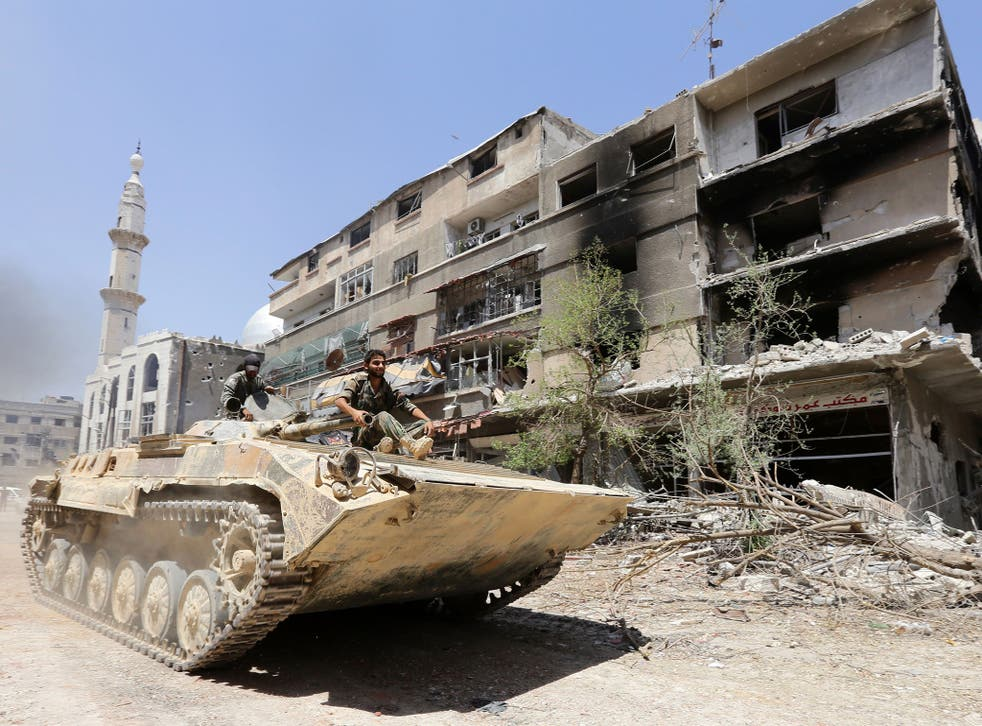 Syrian government troops sit atop a tank as they drive past a damaged building on the outskirts of the capital Damascus