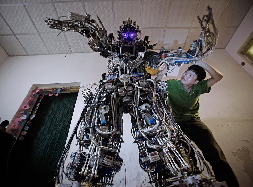 Chinese inventor Tao Xiangli modifies the circuits of his home-made robot at his house in Beijing, May 15, 2013