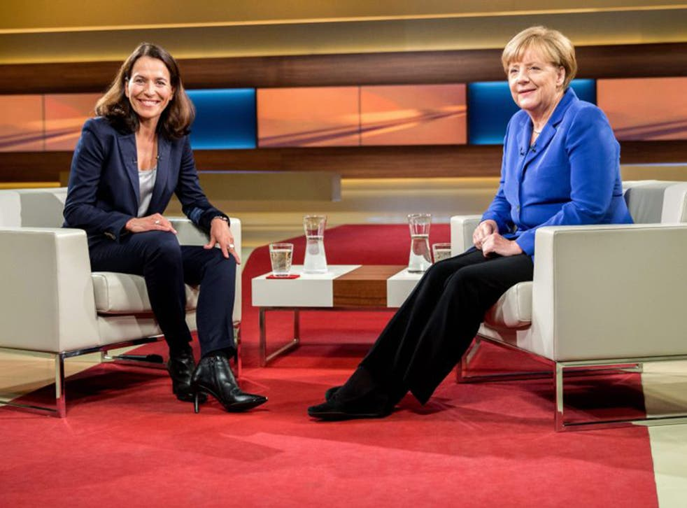Angela Merkel (R) poses with TV host Anne Will prior to the interview in Berlin