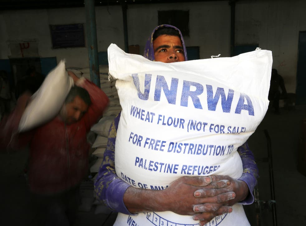 Palestinians receiving their monthly food aid at a UN distribution centre in the Rafah refugee camp, southern Gaza, earlier this year