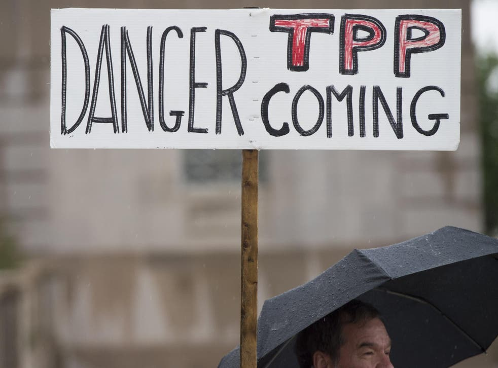 A protestor holds an anti-TPP banner