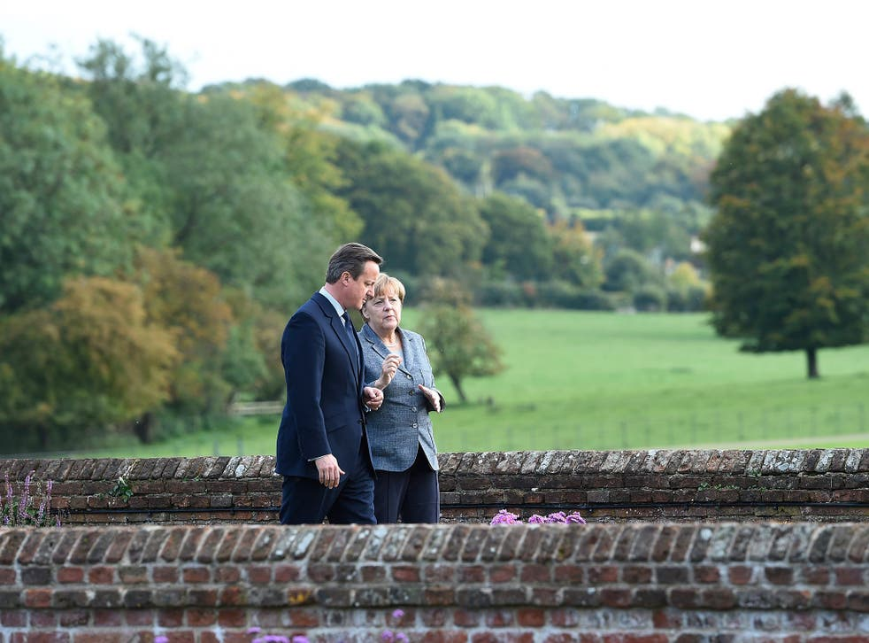 British Prime Minister David Cameron (L) and German Chancellor Angela Merkel (R) chat in the Rose Garden at Chequers in Ellesborough