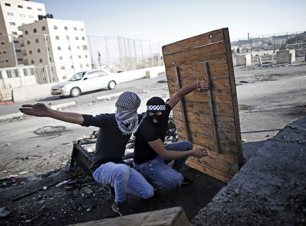 Palestinian demonstraters take shelter as they prepare to throw a molotov cocktail towards Israeli security forces