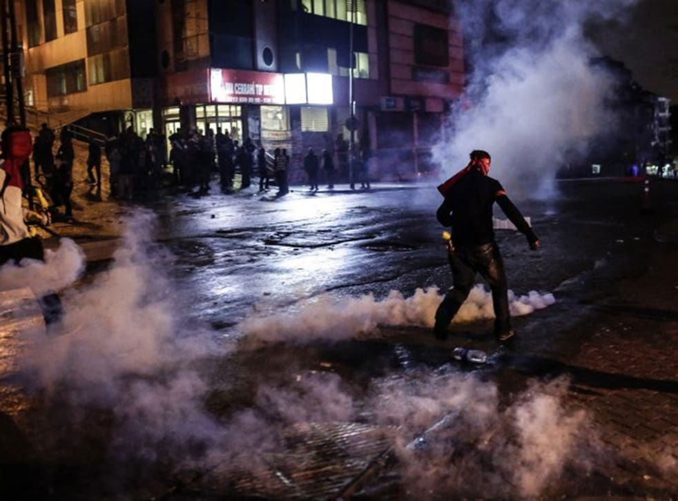 Protesters run away from tear gas during clashes with police on October 10, 2015 at the Gazi district in Istanbul, hours after the deadly attack in Ankara.