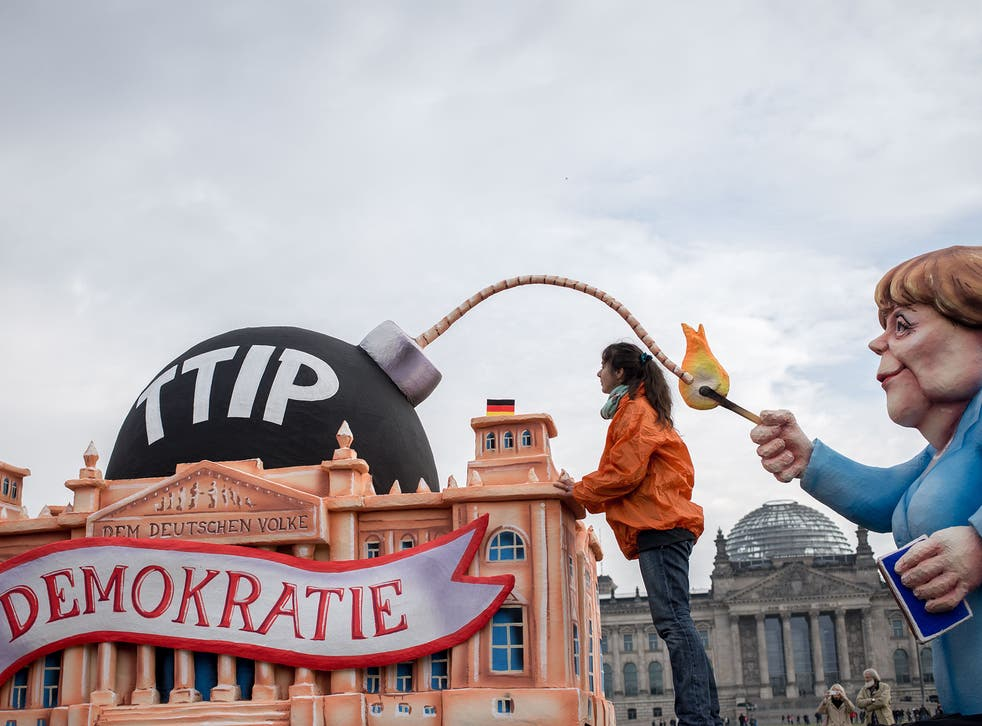Activists work on a float showing Angela Merkel lighting a TTIP-bomb during a demonstration in Berlin, 9 October 2015