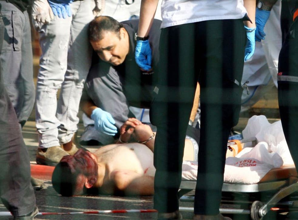 Israeli security forces stand next to a wounded and handcuffed Palestinian man who carried out the stabbing attack