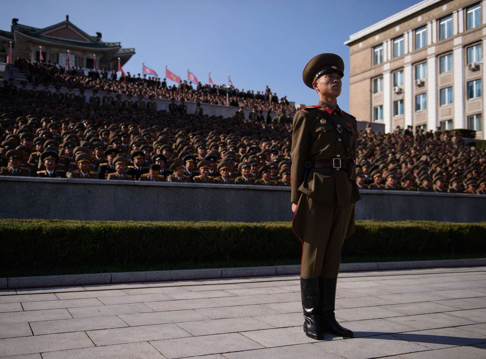 A member of a North Korean honour guard stands before spectators prior to a mass military parade at Kim Il-Sung square