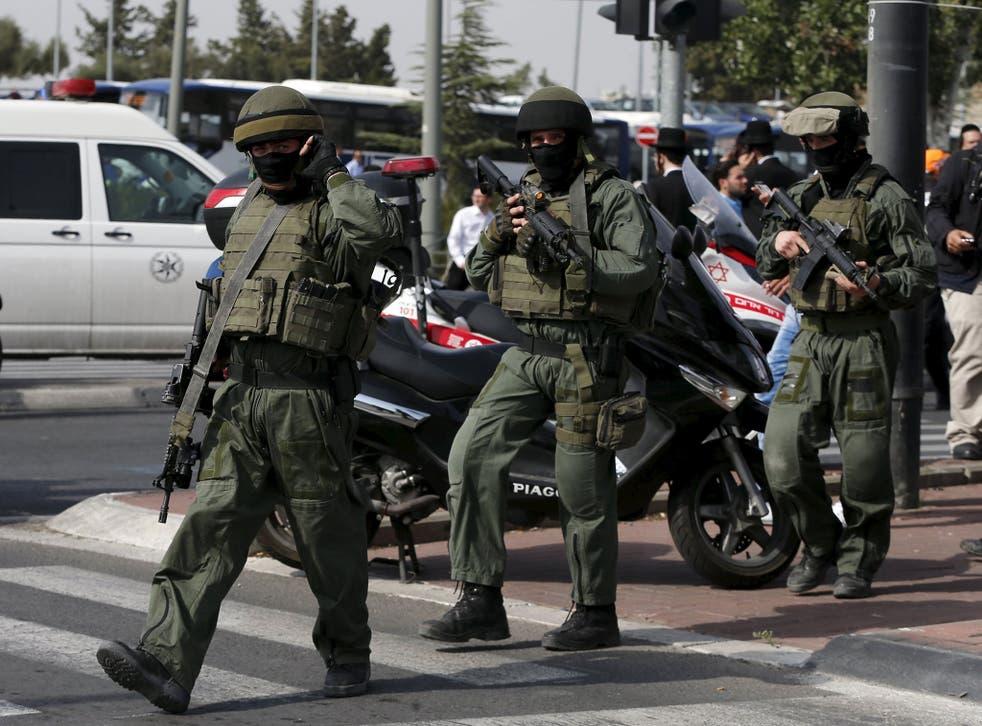 Israeli paramilitary police officers walk near the scene of a stabbing in Jerusalem October 12, 2015.
