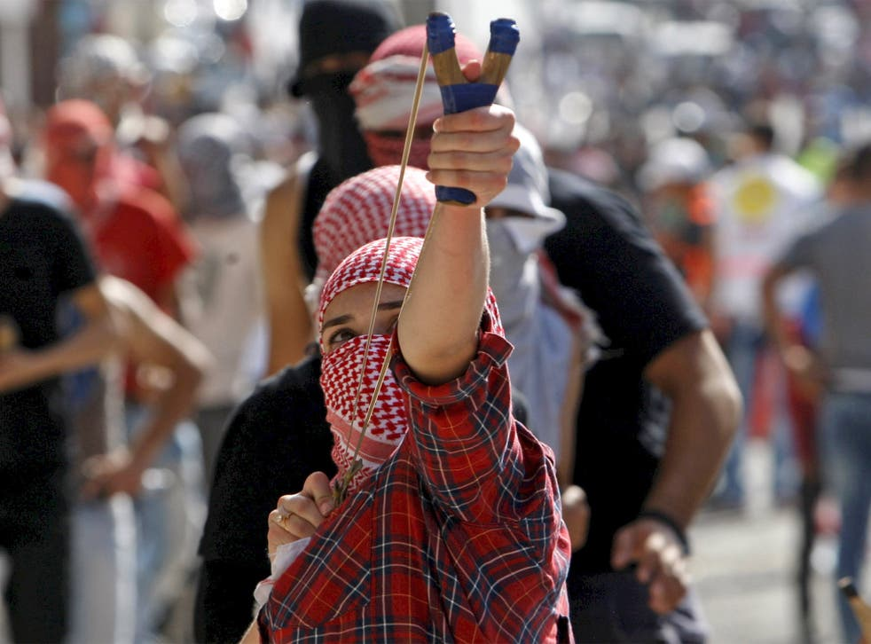 A Palestinian uses a slingshot to throw stones at Israeli troops during clashes in Bethlehem