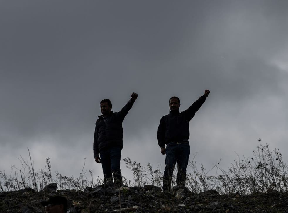 Two men raise their hands in memory of victims of the twin bombings in Ankara. The suicide attack is further polarising relations between Turks and Kurds