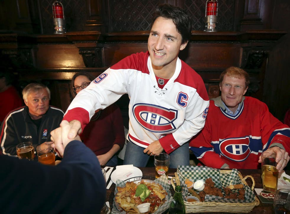 Liberal leader Justin Trudeau shakes hands while watching a Montreal Canadiens hockey game at a bar in Montreal, Quebec,