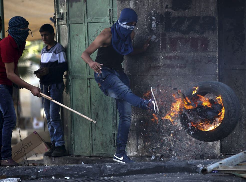A Palestinian protester clashes with Israeli soldiers in Hebron on Saturday