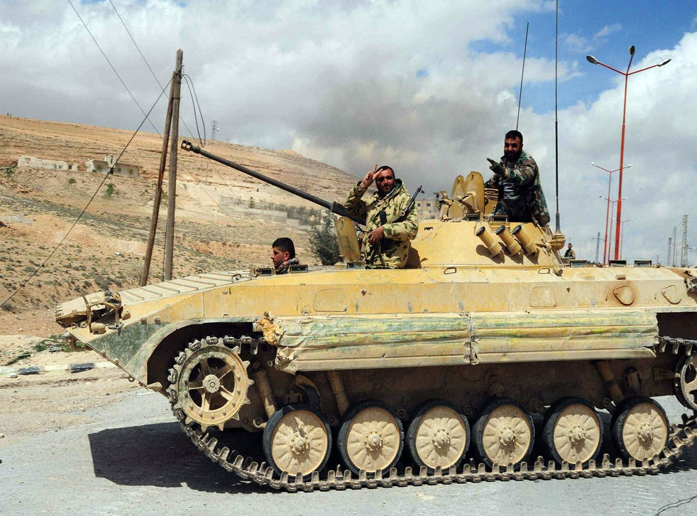 A Syrian army soldier flashes a 'V for victory' sign as his tank travels northeast of Damascus