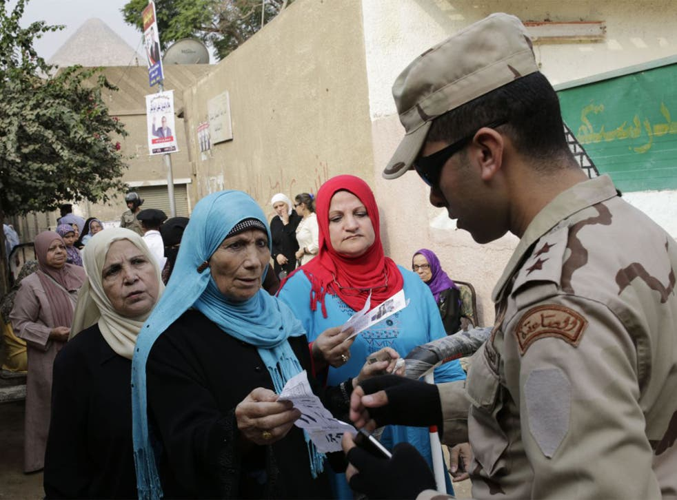 An Egyptian army officer checks documents of voters outside a polling station during the first round of parliamentary elections, in Giza, Cairo