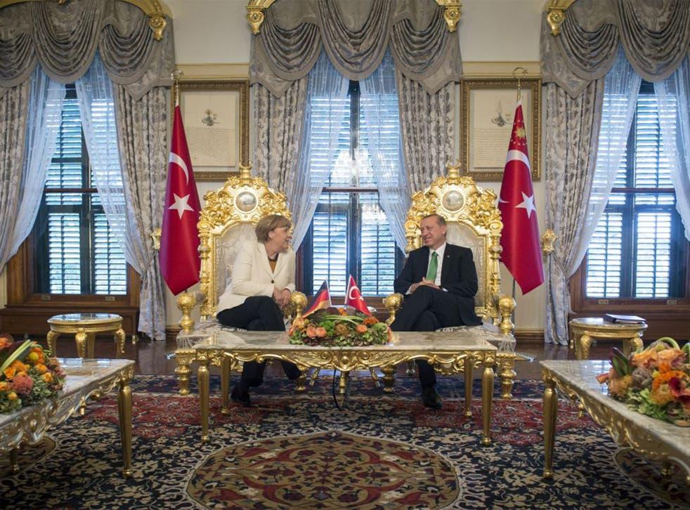 German Chancellor Angela Merkel and Turkish President Recep Tayyip Erdogan talk at the start of their meeting at the Yildiz Palace