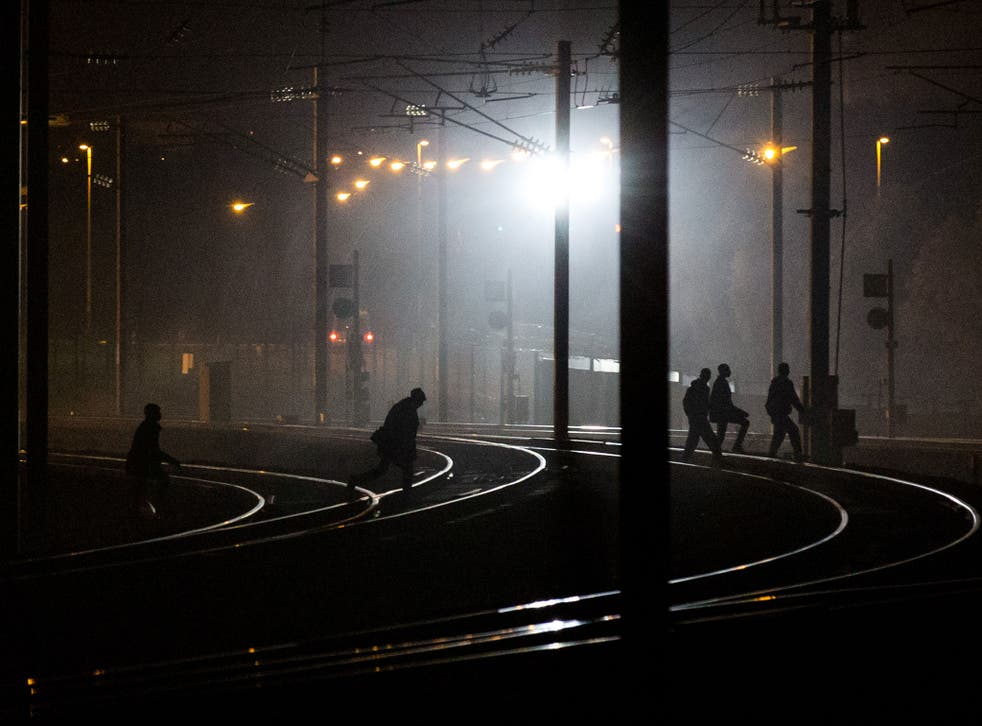 People walk across train tracks near the Eurotunnel terminal in Coquelles on August 3, 2015 in Calais, France.