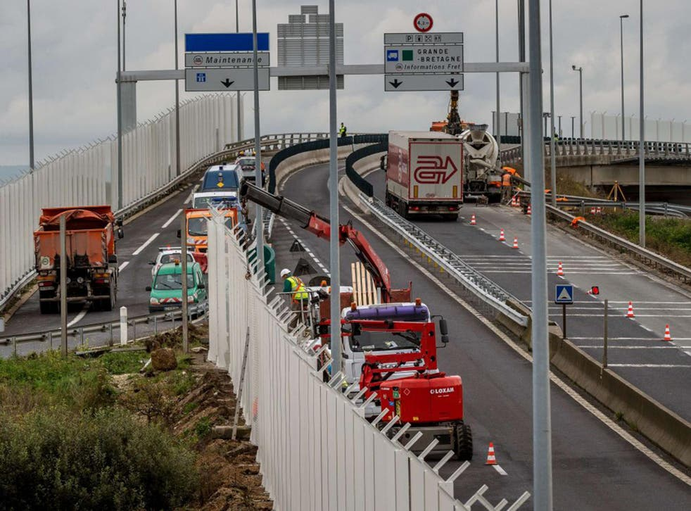 Workers install seven-metre high fencing along the access route to the Eurotunnel in Coquelles to try and prevent migrants from attempting to cross the Channel to Britain