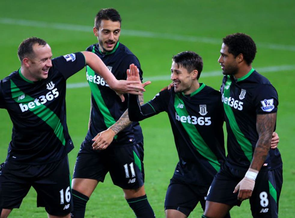 Bojan is mobbed by his Stoke team-mates after his early winner from the penalty spot