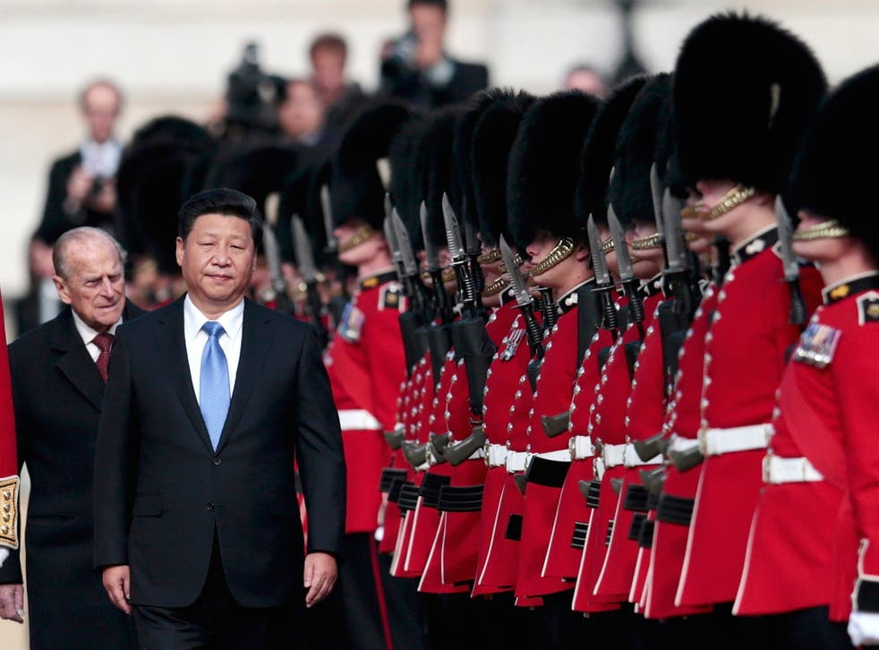 China's President Xi Jinping and Britain's Prince Philip review an honour guard during his official welcoming ceremony in London
