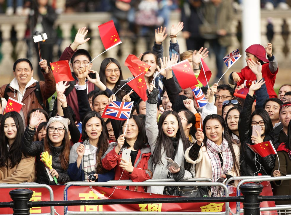 Spectators eagerly wait for the Queen and President Xi Jinping to pass along The Mall