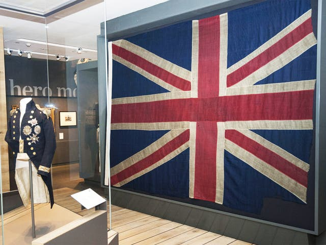 Lord Nelson's uniform next to the Union flag, previously flown at the Battle of Trafalgar, which will go on display to the public at the National Maritime Museum