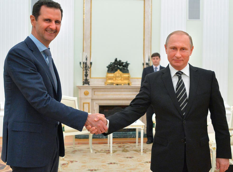 Russian President Vladimir Putin shakes hand with Syrian President Bashar Assad in the Kremlin in Moscow, Russia