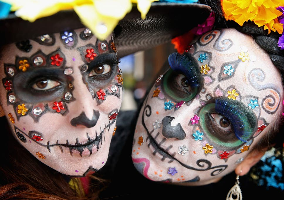 people dress up in vibrant colours and paint their faces to look like skulls during the