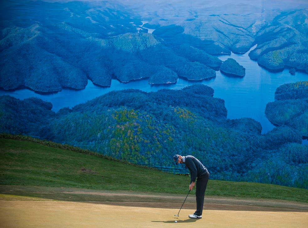 A player puts on the green at the Dragon Lake Golf Club in Guangzhou, China. Golf is seen as providing an opportunity for officials to make shady deals and an extravagance for government employees who should be serving the people