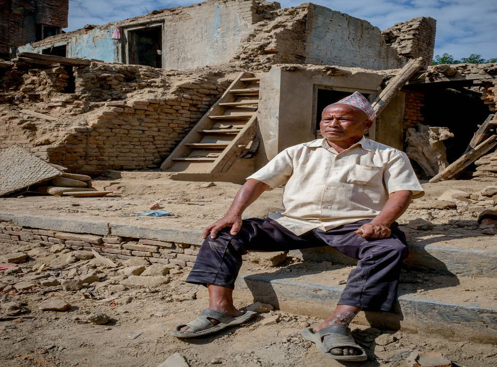 Panchamani Shakya, 66 ,sitting in a pile of rubble where his house once was – overlooking the once-magnificent, now-destroyed Machhendranath Temple in Bungamati, Nepal