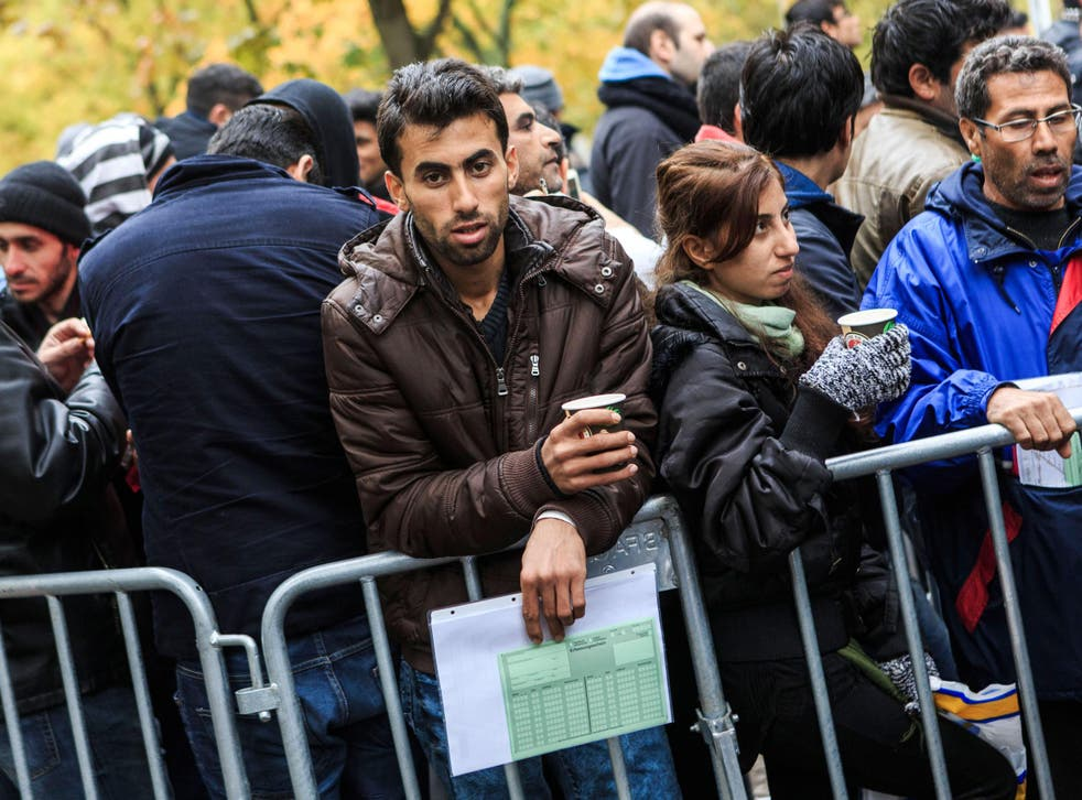 A man seeking refugee status waits to register outside the Central Registration Office for Asylum Seekers in Berlin